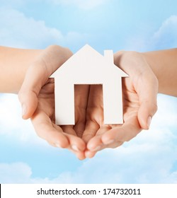 real estate and accomodation concept - closeup picture of female hands holding paper house