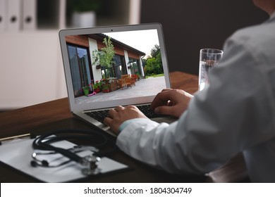 Real estate agency online service. Doctor choosing new house via laptop, closeup