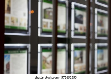 Real estate agency window display at night in London, UK
