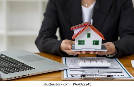 Real estate agent advising clients with contract documents and computers with front view house designs.