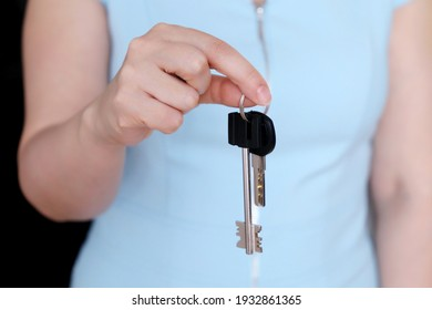 Real estate agent, apartment keys in female hand. Woman in blue dress, concept of purchase or rental home