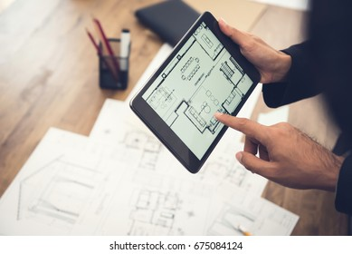 Real estate agent or architect presenting house floor plan to client on tablet computer screen