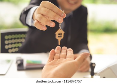 Real estate agent or banker giving a house key to buyer.Concept of housing purchase and insurance.