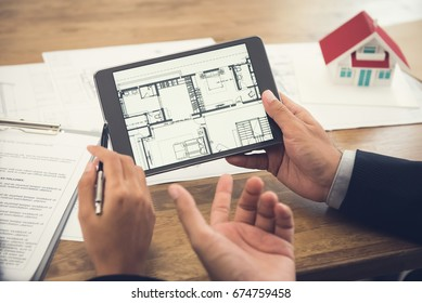 Real estate agent with client or architect team discussing house floor plan on tablet computer screen