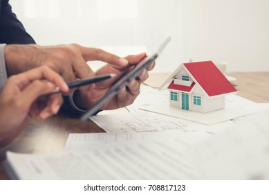 Real estate agent with client or architect team checking a housing model and its blueprints digitally using a tablet
