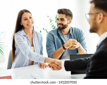 Real estate agent with couple shaking hands closing a deal