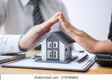 Real estate agent and customer covering Small house model and protection by hands.