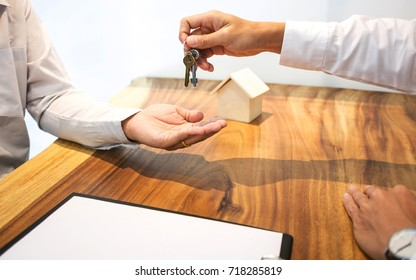 Real Estate agent with customer making contract signature giving a key buy / rent a house