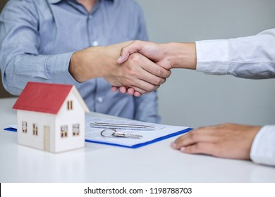 Real estate agent and customers shaking hands together celebrating finished contract after signing about home insurance and investment loan, handshake and successful deal.