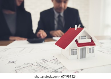 Real estate agent discussing work with blueprints and house model on the table - property appraisal and valuation concept