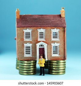 A real estate agent in front of a house on gold coin stilts, asking the question how much money will you have to invest to purchase this property?
