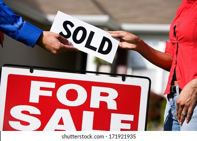 Real Estate: Agent Giving Buyer Sold Sign