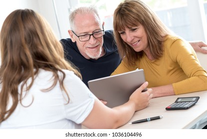 Real estate agent giving explanations on tablet to senior couple