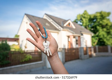 Real estate agent giving house keys to a new property owner on blurred background