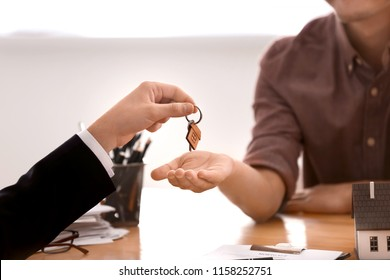 Real estate agent giving key of new house to man in office