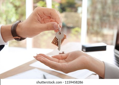 Real estate agent giving key to woman in office, closeup
