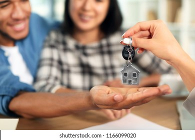 Real estate agent giving key from new house to happy interracial couple in office, closeup
