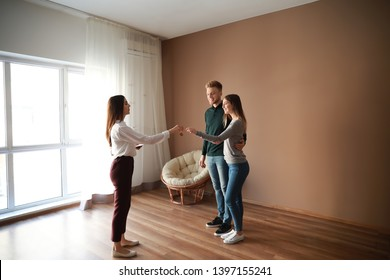 Real estate agent giving a key from new house to young couple
