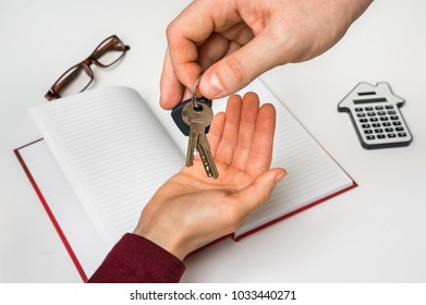 Real estate agent giving keys from new house to young woman - real estate sale concept