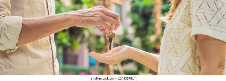 Real estate agent giving keys to apartment owner, buying selling property business. Close up of male hand taking house key from realtor. Mortgage for purchasing flat, getting access to own home BANNER