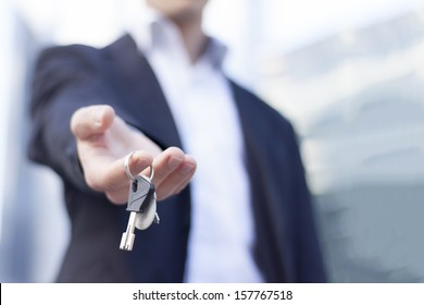 Real estate agent giving keys with buildings background