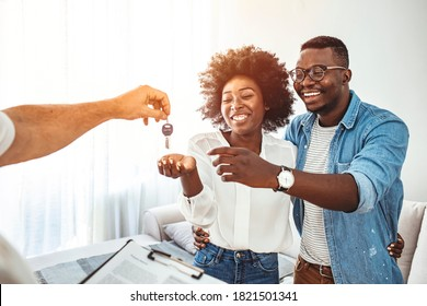 Real estate agent giving keys to couple of customers. Happy young couple getting keys of their new home. Real estate agent giving a key from new house to young couple