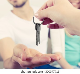 Real estate agent giving keys to young couple, closeup
