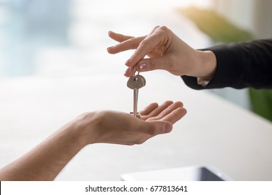 Real estate agent giving keys to apartment owner, buying selling property business. Close up of male hand taking house key from realtor. Mortgage for purchasing flat, getting access to own home