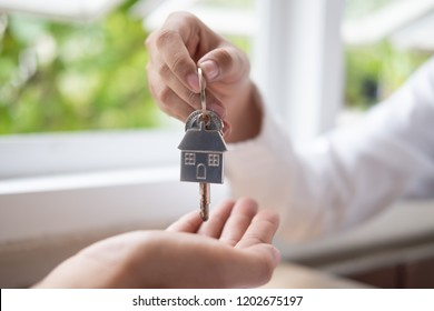 Real estate agent hand giving a house keys to house buyer.
