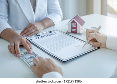 The real estate agent hand holding money and explains the business contract, rent, purchase, mortgage, a loan, or home insurance to the man buyer.