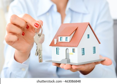 Real estate agent hand over property or new home keys to a customer