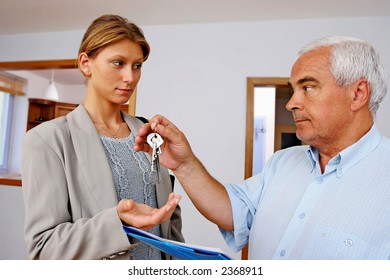 real estate agent handing keys to client, buyer