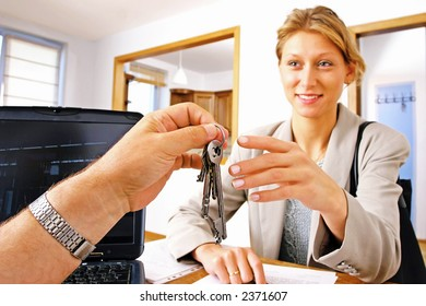 real estate agent handing keys to client, buyer