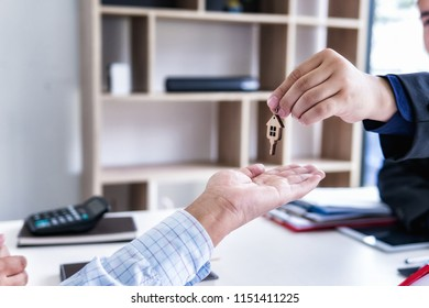 Real estate agent handing over a house key on the rental agreement or the buy home contracts with the real estate property. Mortgage concept.