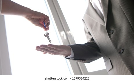 Real estate agent handing over a key to a customer on the window background