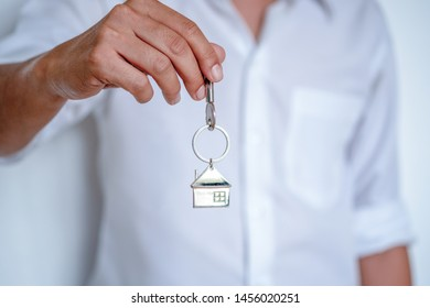 Real estate agent handing over house keys, Men hand holding key with house shaped keychain, Close up focus.