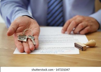 Real estate agent handing over house keys with approved mortgage application form