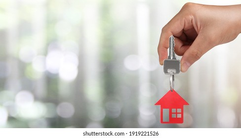 Real estate agent handing over a house keys in hand, and coins