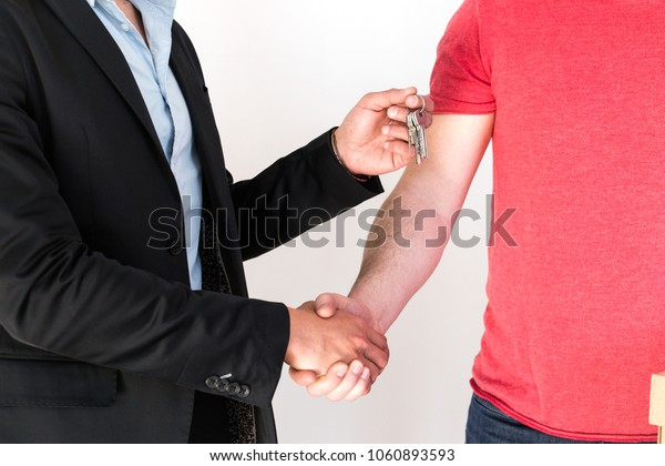 Real estate agent hands over the keys to the new house to the new owner shaking hands