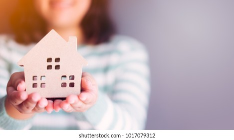 Real estate agent holding house model on gray background.sell house business concept.housewife holding wooden house protection and show.home loan, finance and mortgage concept.