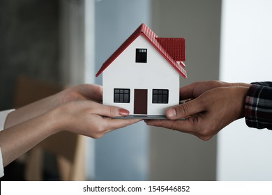 Real estate agent holding house model and pass to customer, Property concept.