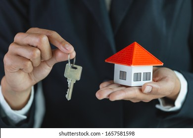 Real estate agent holding house model and keys,  customer signing contract to buy house, insurance or loan real estate.