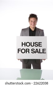 Real estate agent holding a House For Sale sign