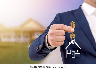 Real estate agent holding keys in front of a beautiful new home.