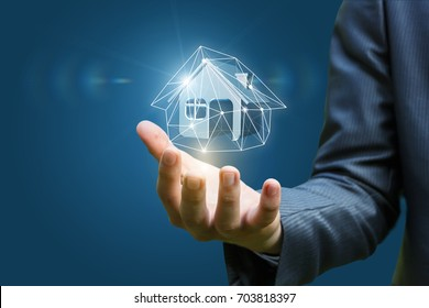 Real estate agent holding a model house on a blue background.