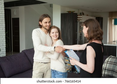 Real estate agent holding rental agreement shaking hands to young smiling couple, friendly realtor making deal with clients after showing house to renters, tenants happy to rent new home