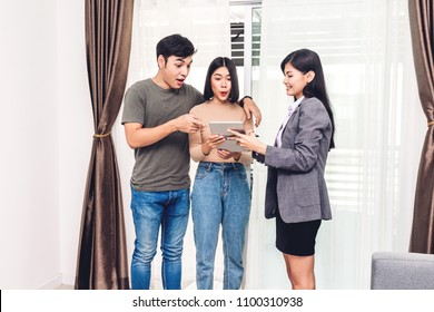 Real estate agent holding tablet and talk with young couple in a house for sale. business and real estate concept