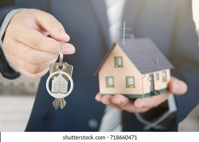 Real estate agent with home keys and house miniature. realestate key apartment real estate home house homeowner concept