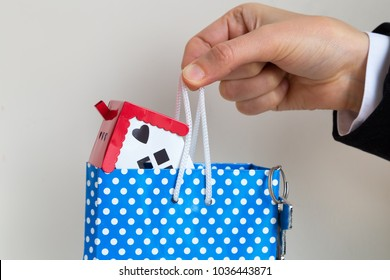 Real estate agent with house model and key, mortgage investment. Being an easy way homeowner.the hand hold the house in the bag.