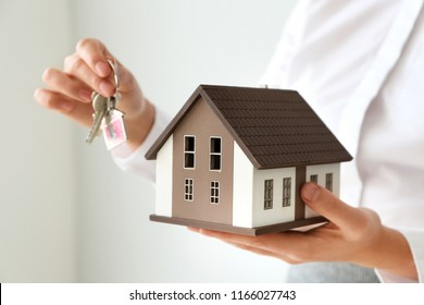 Real estate agent with house model and key on light background, closeup